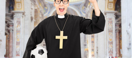 Priest cheering and holding a football